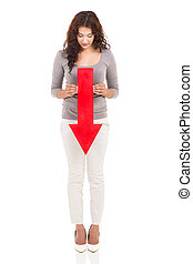 woman holding red arrow pointing down - full length portrait...