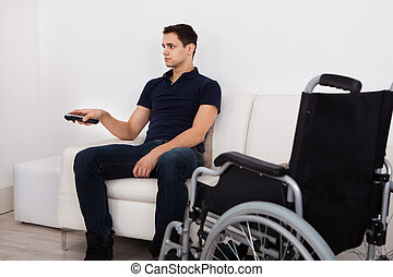 Handicap Man Using Remote Control While Watching Television...