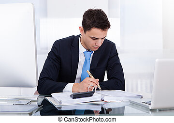Businessman Computing Tax - Young businessman computing tax...