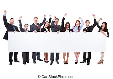 Large group of excited businesspeople presenting banner -...