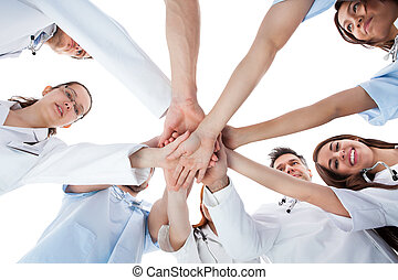 Doctors and nurses stacking hands. Isolated on white