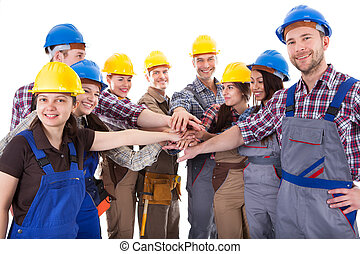 Diverse group of construction workers stacking hands...