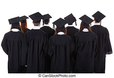 Large group of students graduating standing in the gowns and...