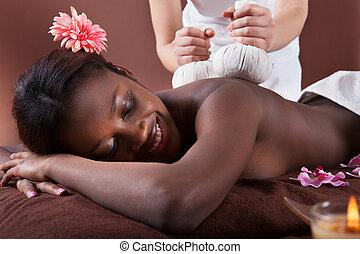 Woman Enjoying Herbal Massage At Spa