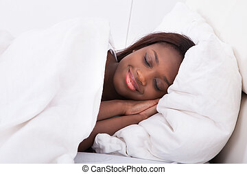 African American woman sleeping in bed - Smiling African...
