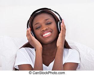 mujer, el gozar, Música, por, auriculares, en, Cama