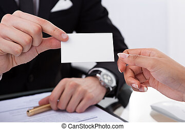 Businessman Giving Business Card To Colleague - Cropped...
