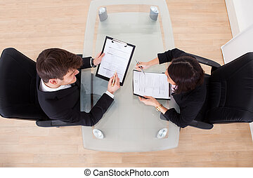 Business People Discussing Over Documents - High angle view...