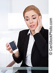 Businesswoman Holding Smartphone With Cracked Screen -...