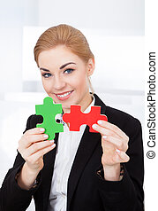 Businesswoman Holding Jigsaw Puzzle
