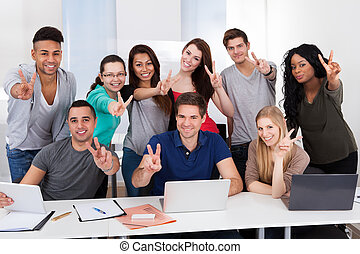 College Students Gesturing Victory Sign Together - Group...