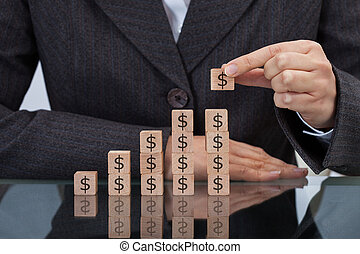 Businesswoman Stacking Dollar Blocks - Midsection of...