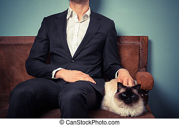 Young man and cat relaxing on sofa - A young man is sitting...
