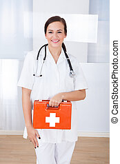 Happy Female Doctor Holding First Aid Box - Portrait of...