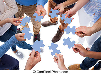 Group of people connecting puzzle pieces - High angle view...