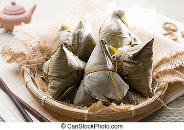 Zongzi - Asian Chinese rice dumplings on basket, tea at...