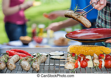 Food serving - A man putting a grilled sausage on a plate