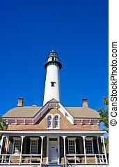 White Lighthouse Behind Brick House