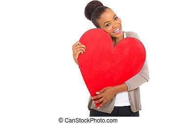 afro american woman hugging a heart shape - cheerful afro...