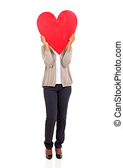 young woman hiding her face behind heart shape
