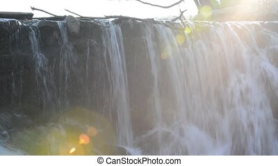 Waterfall and sun ray pan from left - Water Cascade on a...