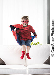 Little super hero - Super hero boy jumping and playing on...