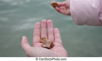 Girl throw stones  into the sea