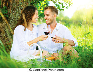 Picnic. Young Couple relaxing and drinking Wine in a Park