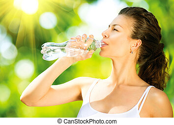 Healthy and Sporty Young Woman Drinking Water from the...