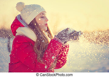 Beauty Winter Girl Blowing Snow in frosty winter Park....