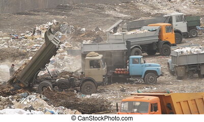 Garbage machines unload garbage on a municipal dump in...