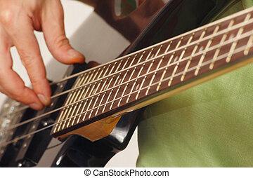 Guitarist playing the electric bass guitar closeup