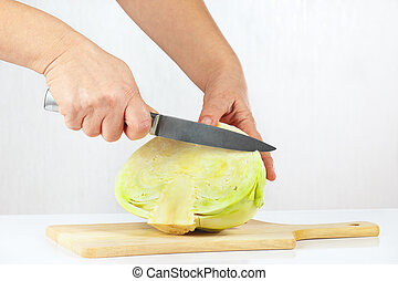 Female hand cuts fresh cabbage - Female hand cuts cabbage on...