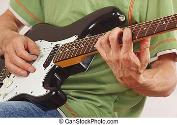 Guitarist put fingers for chords on electric guitar closeup