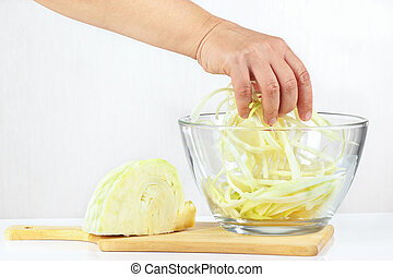 Female hand mixes shredded cabbage in a glass bowl closeup