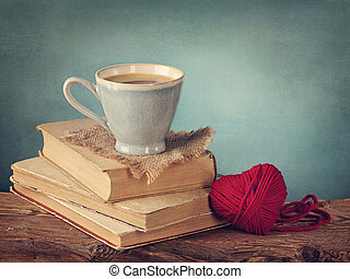 Cup of coffee standing on old books