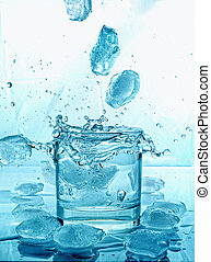 tumbling ice cubes in glass of water on a glass table