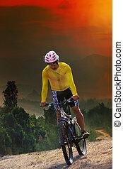 young man riding mountain bike bicycle crossing mountain...