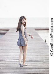 beautiful asian woman walking on wood pier with relaxing...