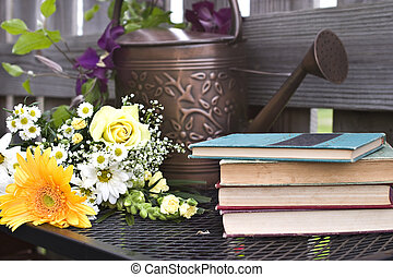 Watering can and old books with a clematis vine
