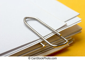 paper clip  - view of a paper clip with stack of blank paper