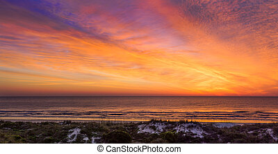 Colorful Coastal Daybreak - The rising sun illuminates the...
