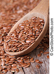 Flax seeds in a wooden spoon macro. Vertical - Flax seeds in...