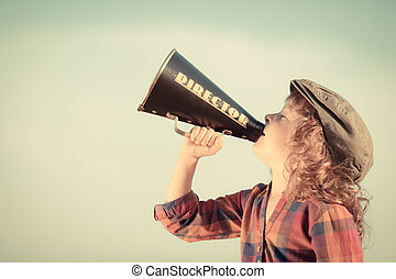 Kid shouting through vintage megaphone Communication concept...