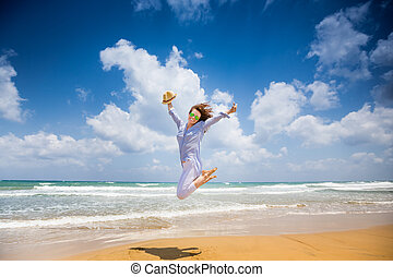 Happy woman jumping at the beach Summer vacations and...