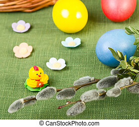 Pussy willow flower branch with easter eggs on green...