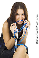 Woman gnawing beads sitting in black dress with long hair...