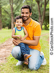 happy indian father and son outdoors in forest