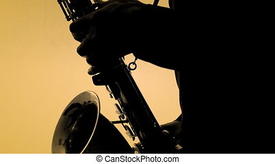 Man playing sax in silhouette. Close-up - Man playing sax in...