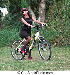 Pin-up girl poising on a bike - a young beautiful pin-up...